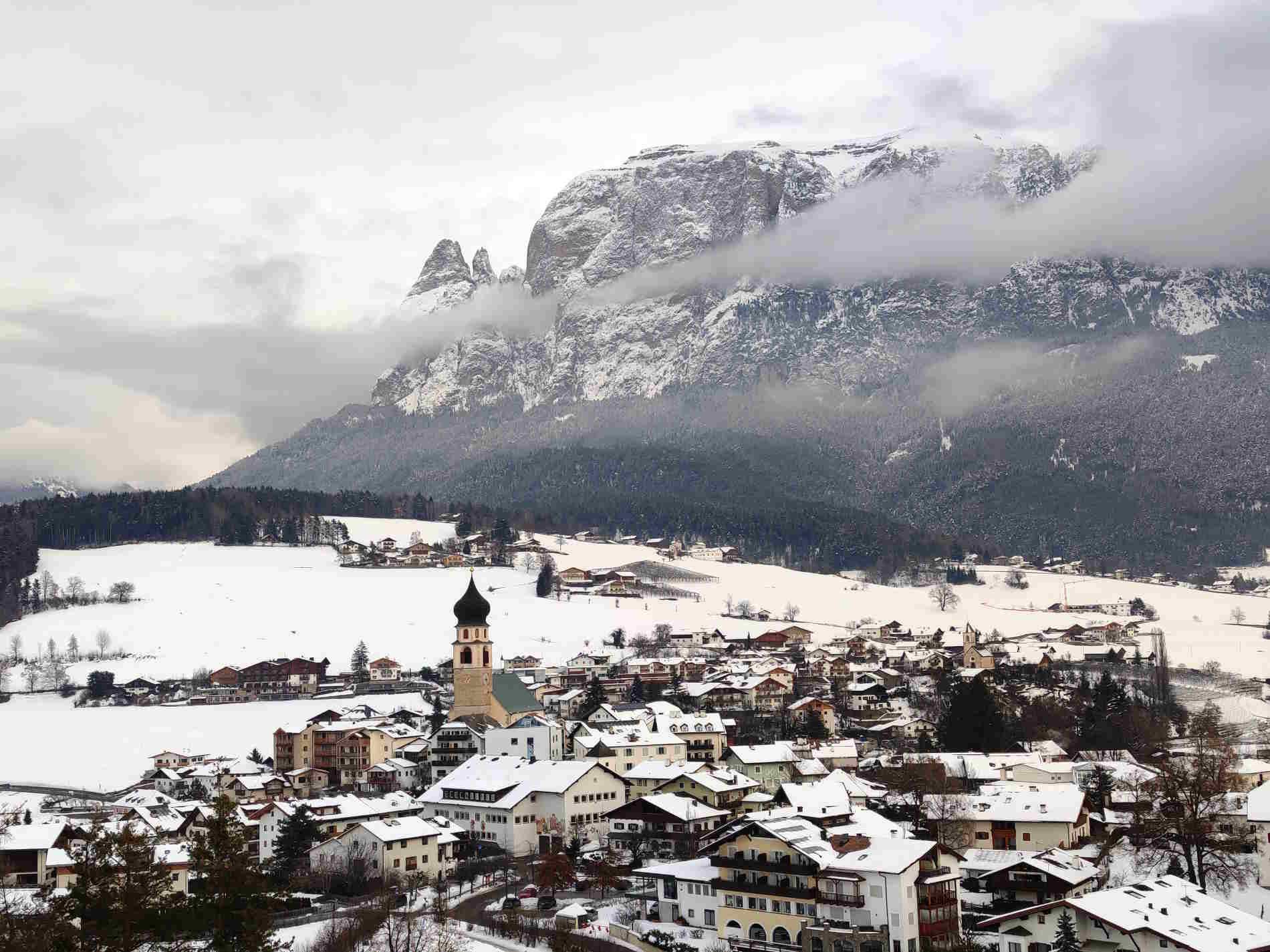 Panorama invernale sul borgo di Fiè allo Sciliar e sul massiccio dello Sciliar nelle Dolomiti altoatesine